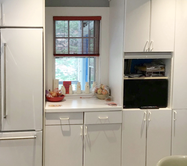 Before photo of dated white kitchen with TV in cabinets