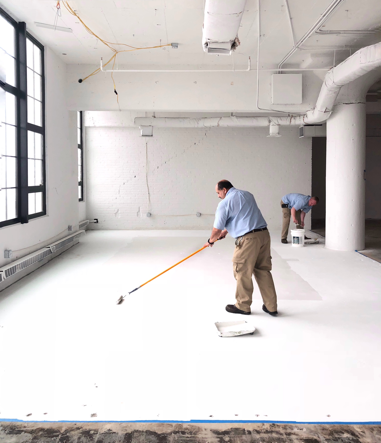 men painting white floor in loft space