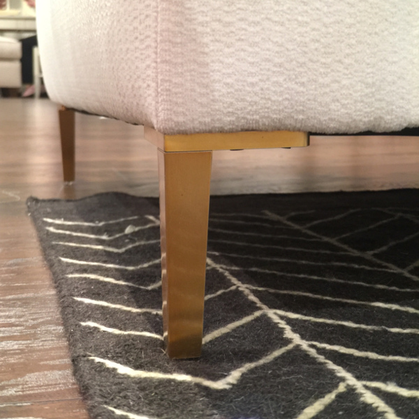 brass gold  metal legs on base of white sofa