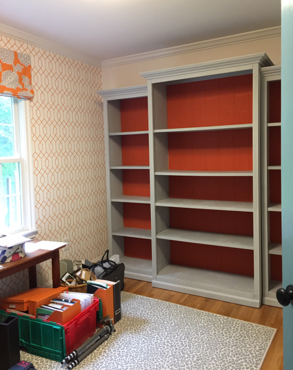 gray painted bookcase with orange back