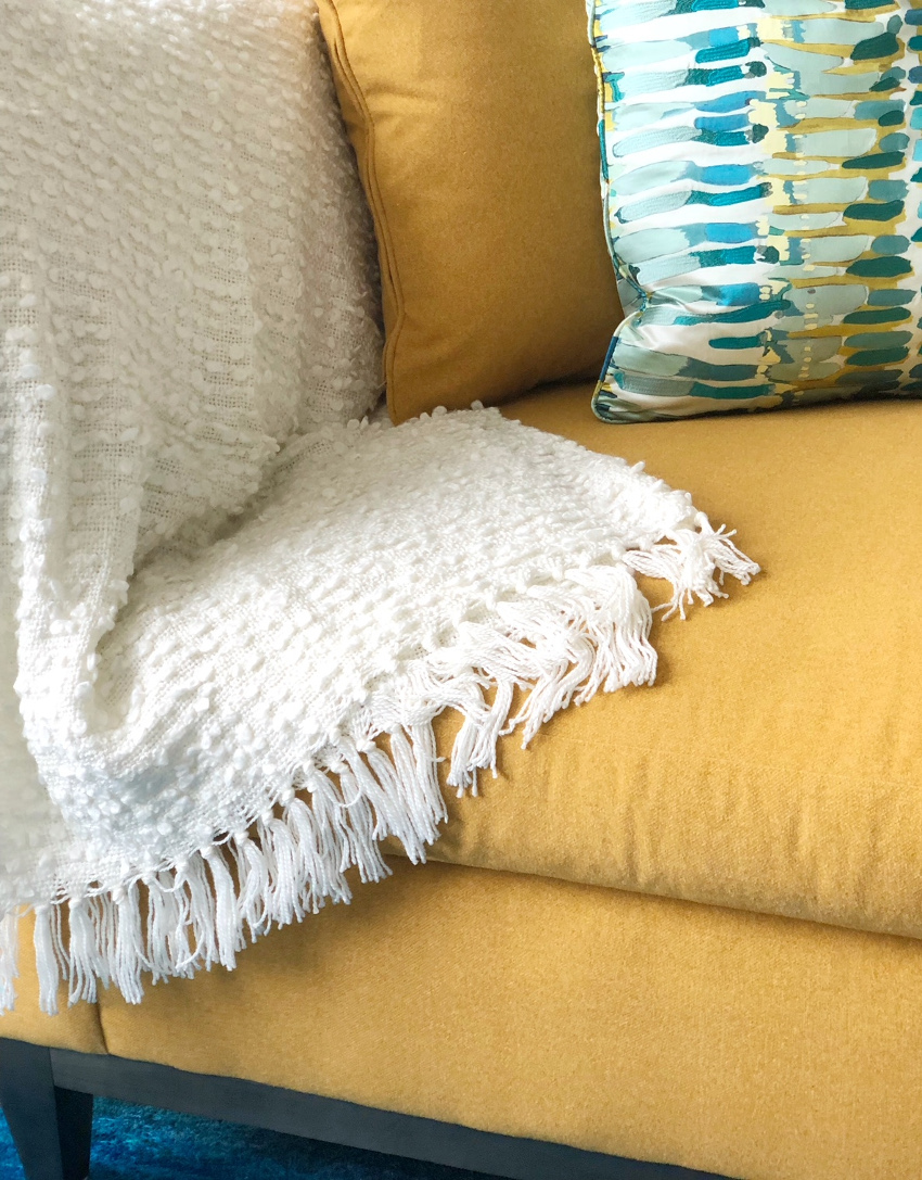 white throw on yellow sofa